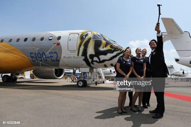 Flight attendants take a selfie photograph in front of a prototype of the Embraer SA E190 E2 passenger aircraft on display during a media preview day...