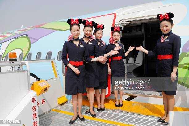 Flight attendants wait for passengers at a Disney Pixar Toy Story-themed aircraft launched by China Eastern Airlines before its maiden flight from...