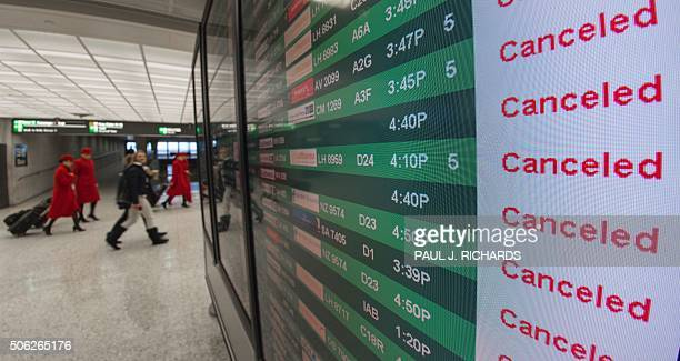 Flight attendants walk near the flight status board for arrivals and departures at Dulles International Airport just outside Washington DC January 22...