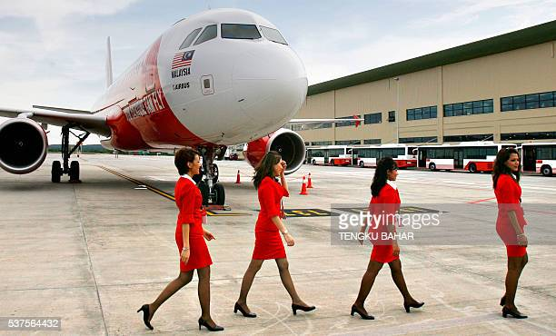 Flight attendants walk past an Air Asia airbus A320 parked next to the newlyopened Low Cost Carrier Terminal at the Kuala Lumpur International...