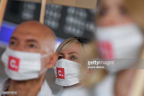 Flight attendants wear masks during a demonstration through the Terminal 1 at Frankfurt am Main airport Germany 14 July 2017 The public services...