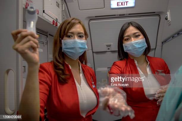 Flight attendants wearing facemasks as protection from COVID-19 record the temperatures of passengers boarding an AirAsia flight bound for Manila,...