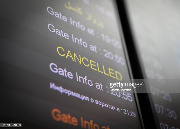flight cancelled illuminated on airport arrivals board - mid air stock pictures, royalty-free photos & images