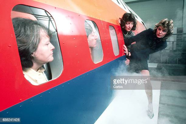 Flight crew aboard a United Boeing 767 flight simulator evacuate through a door over the wing as passengers look on through windows The flight crew...