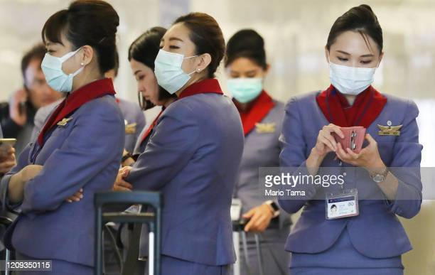 Flight crew from China Airlines, wearing protective masks, stand in the international terminal after arriving on a flight from Taipei at Los Angeles...