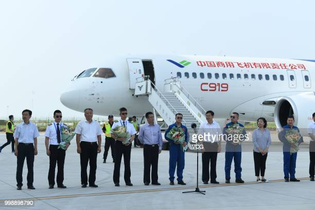 Flight crew members line up after the No102 C919 passenger jet lands at Dongying Shengli Airport on July 12 2018 in Dongying Shandong Province of...