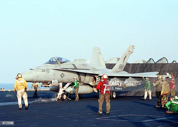 """Flight crew prepare an F/A-18C """"Hornet"""" for launch November 17, 2001 from the deck of the aircraft carrier USS Carl Vinson. The Vinson and her..."""