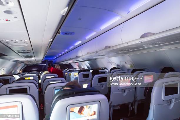 Flight crew walk down the aisle of a Virgin America aircraft featuring purple mood lighting September 26 2016