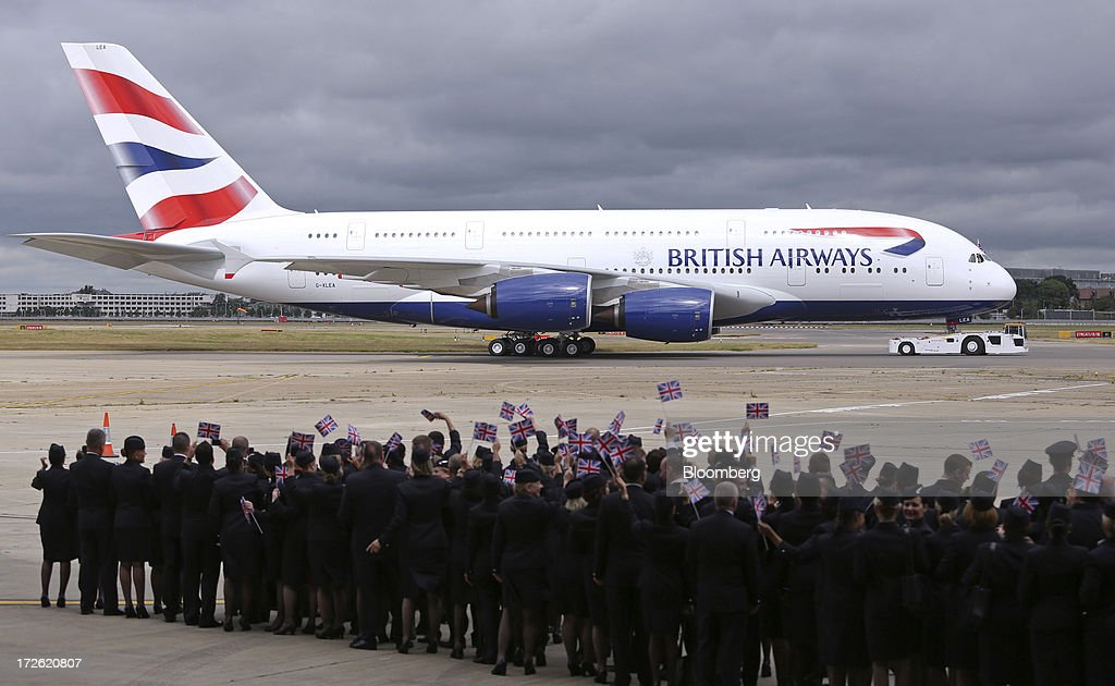 Flight crews wave British Union flags as the new Airbus A380 operated by British Airways (BA) is pulled by a tractor after landing at Heathrow airport in London, U.K., on Thursday, July 4, 2013. British Airways will start regular services with the Airbus SAS A380 superjumbo a week earlier than planned after taking delivery of the first of 12 of the doubledeckers today. Photographer: Chris Ratcliffe/Bloomberg via Getty Images