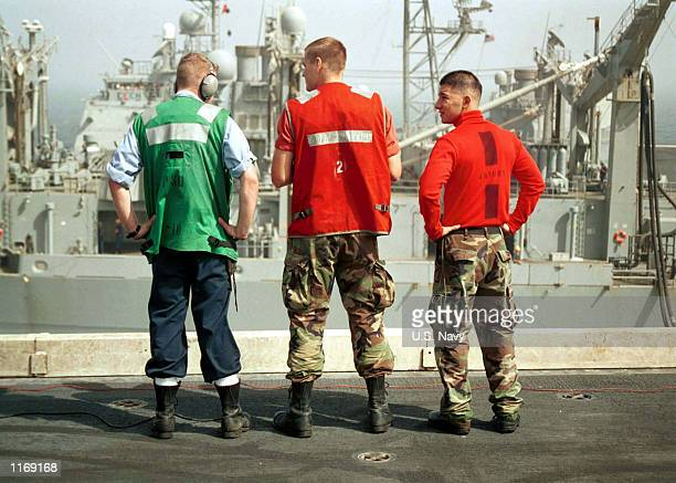 Flight deck sailors observe a ship-to-ship replenishment effort while onboard the USS Carl Vinson October 12, 2001 at sea.