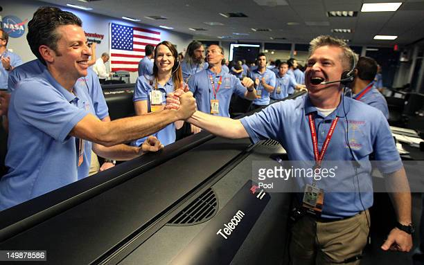 Flight director Keith Comeaux right celebrates with Martin Greco after a successful landing inside the Spaceflight Operations Facility for NASA's...