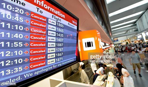 A flight information board displays cancelled flights due to Typhoon Halong at Tokyo's Haneda airport departure lounge on August 9 2014 The strong...