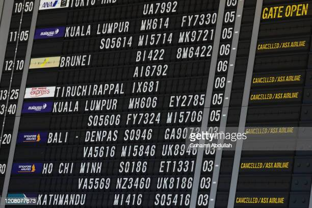 Flight information board is seen at Changi Airport on March 24, 2020 in Singapore. Singapore will not allow short term visitors to enter or transit...