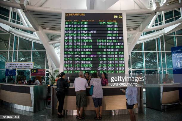 A flight information board shows a list of flights some still cancelled due to Mount Agung volcano at Ngurah Rai International Airport in Denpasar on...