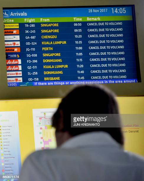 A flight information board shows the list of delayed flights due to the volcano at the Ngurah Rai International airport in Denpasar Bali on November...