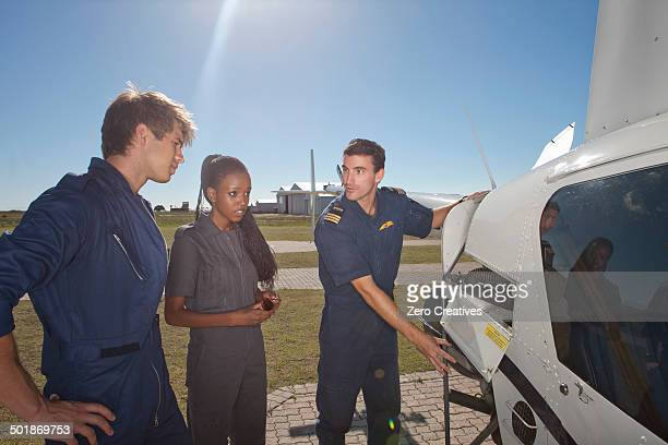 Flight instructor showing student pilots engine of helicopter