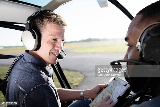 flight instructor teaching young man in helicopter - inside helicopter stock pictures, royalty-free photos & images