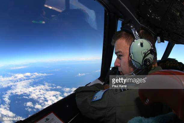 Flight Lieutenant Russell Adams looks out from the cockpit of an AP-3C Orion whilst on a search mission in the Southern Indian Ocean on March 26,...