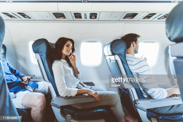 flight passenger making a phone call - izusek stock pictures, royalty-free photos & images