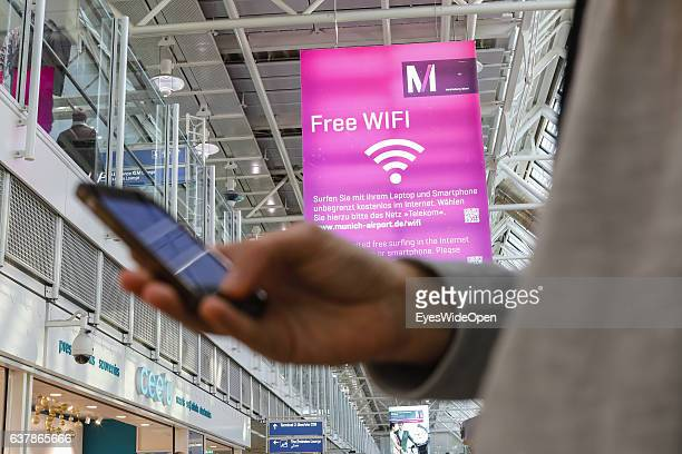 Flight passenger uses free Wifi with his handy on the way to Myanmar via Dubai at Munich Airport on December 04 2016 in Munich Germany