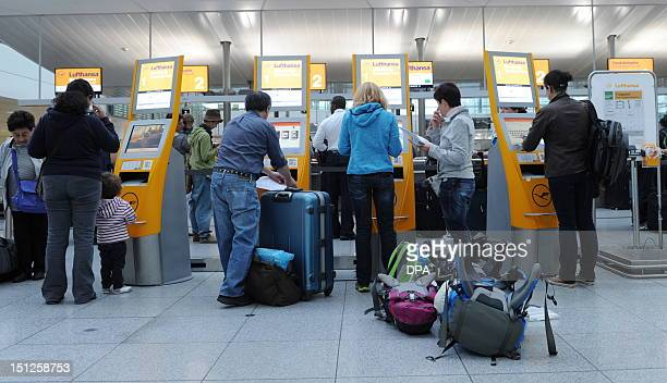 Flight passengers use the Lufthansa selfcheckin desks at the FranzJosefStrauss airport in Munich southern Germany on early September 5 2012 German...