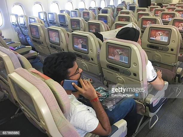 Flight passengers with mobile phone use entertainment program on screens on board of a Airbus A 380 on the way to Myanmar via Dubai at Munich Airport...