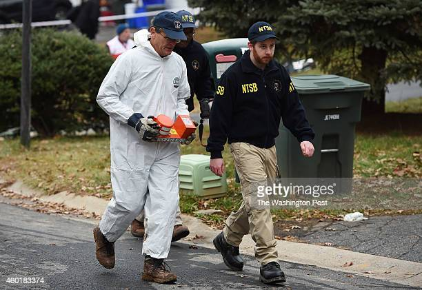 A flight recorder is carried from a plane that went down in a neighborhood on Monday December 08 2014 in Gaithersburg MD