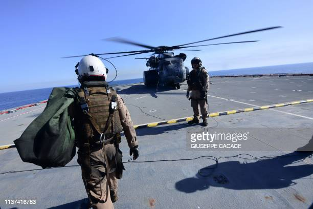 A flight specialist walks towards an MH53E Sea Dragon on the deck of the Lewis B Puller carrier during a joint demining drill between the US British...