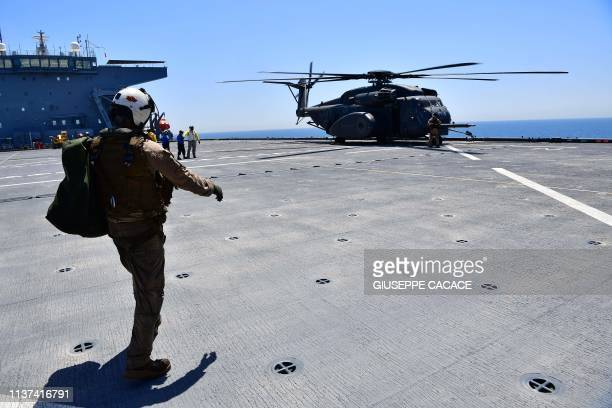 Flight specialist walks towards an MH-53E Sea Dragon on the deck of the Lewis B. Puller carrier during a joint demining drill between the US, British...