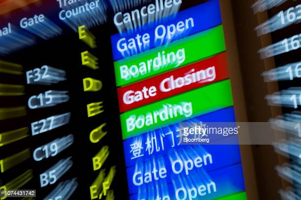 Flight statuses are displayed on a departure board at Terminal 3 of Changi Airport in Singapore on Thursday Dec 13 2018 Singapore'sChangiAirport...