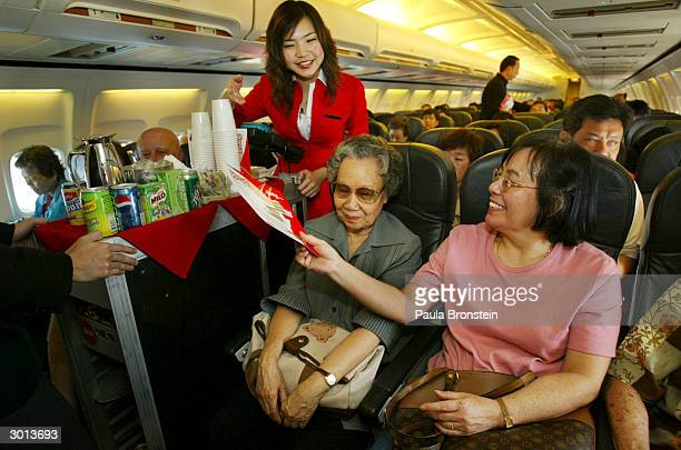 A flight stewardess is seen serving drinks and snacks on board the Air Asia Boeing 737300 flight from Bangkok to Phuket on February 25 2004 in...