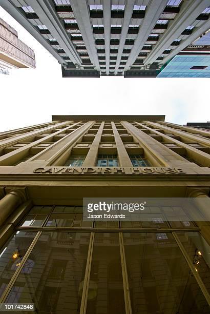 A city Art Deco apartment facade opposite a modern office complex.
