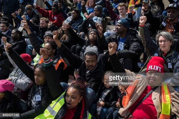 Flint residents and allies from regions nearby pose for a group photo during a protest on the steps of the Michigan State Capitol on April 11 2018 in...