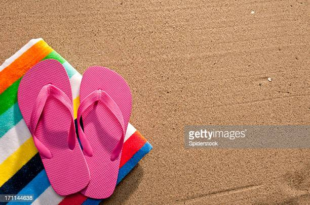 Flip Flops And Beach Towel On Sand