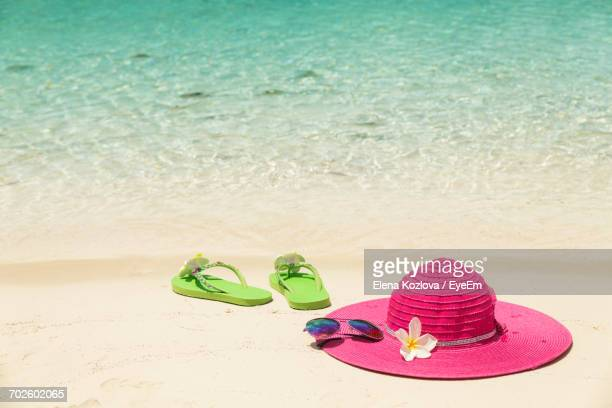 flip flops and sun hat on sand at beach - sun hat stock pictures, royalty-free photos & images
