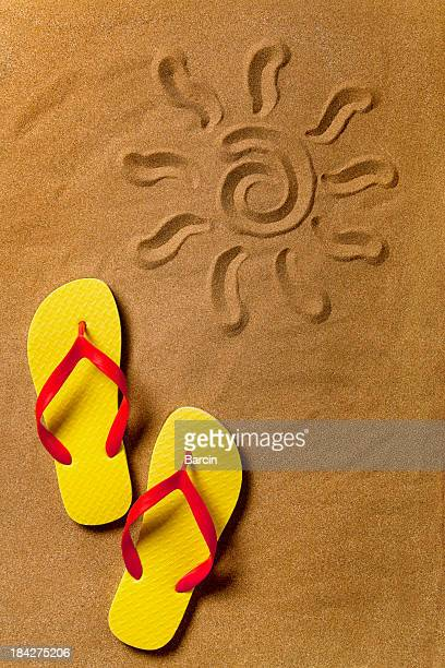 Flip flops and sun sign on the sand