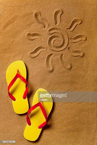 Flip flops y el signo en la arena de la playa