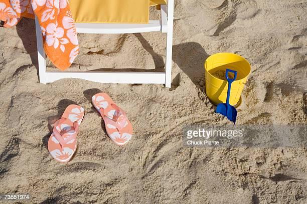Flip flops, deck chair, bucket and spade on sand