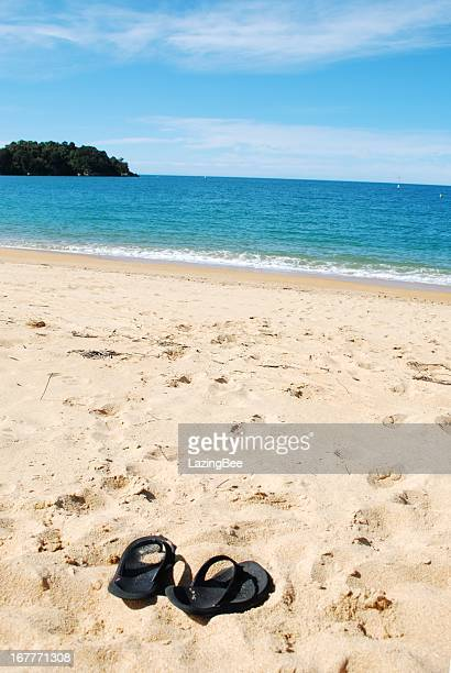 Flip flops in the sandy beach before the bright blue water