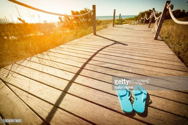 flip flops on a wooden footpath to the beach on the dunes at sunset - flip flops stock pictures, royalty-free photos & images