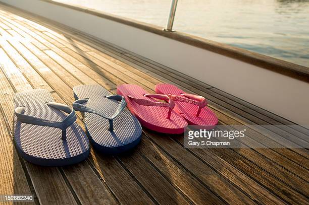 Flip flops on teak deck of 62 ft sailboat