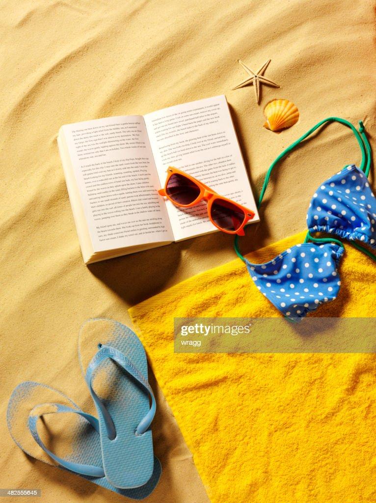 27dbea9e1faf1 Flip-Flops am Strand mit Handtuch und offenes Buch   Stock-Foto
