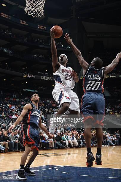 Flip Murray of the Atlanta Hawks puts up a shot against Raymond Felton of the Charlotte Bobcats at Philips Arena on December 15 2008 in Atlanta...
