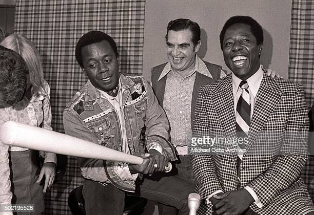 Flip Wilson swings a bat as Hank Aaron laughs during a press conference before filming NBCTV's The Flip Wilson Show on October 15 1973 in Hollywood...