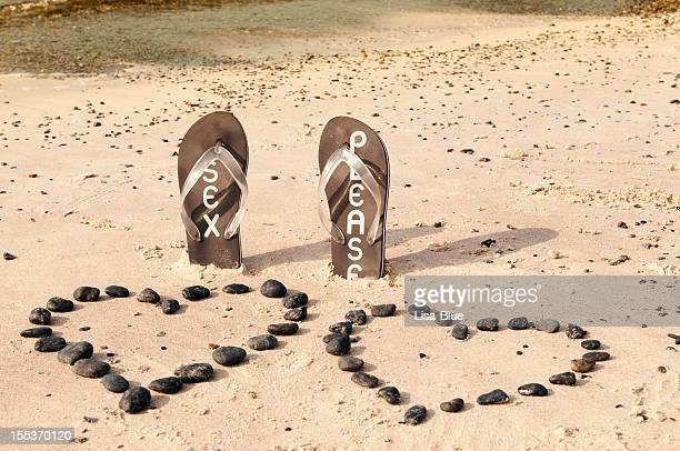flip-flop on the sand - heart month stock photos and pictures