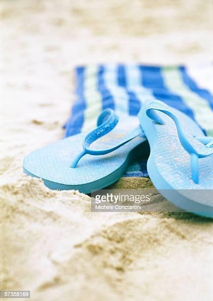 Flipflops and beach towel on beach