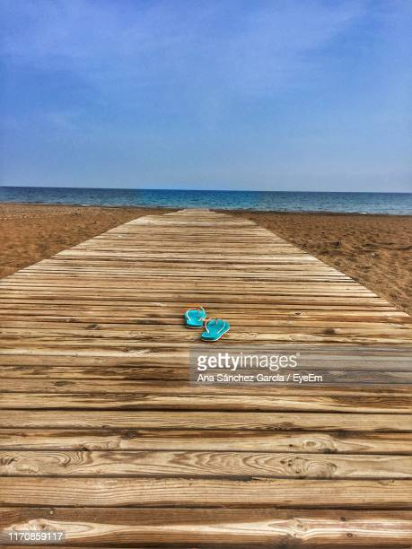 flip-flops on boardwalk at beach against blue sky - flip flop stock pictures, royalty-free photos & images