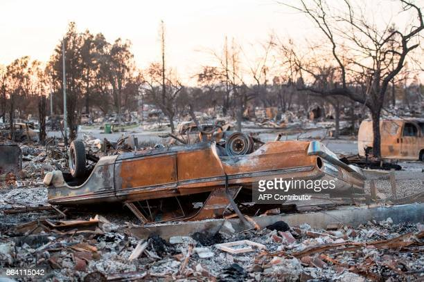 A flipped burned out car is seen among debris and rubble where an entire neighborhood was destroyed during the fires in Santa Rosa California on...