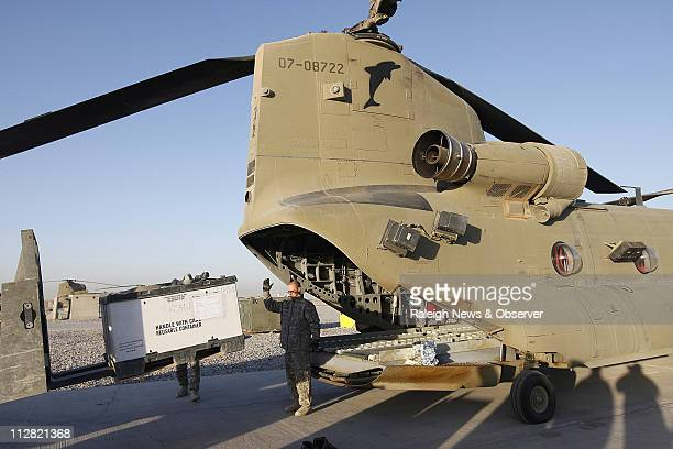 Flipper 12 crew chief Sgt Jeffrey Sherwood directs a forklift operator loading cargo into the back of the CH47F Chinook helicopter assigned to 382nd...