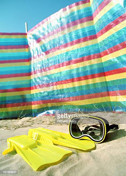 Flippers and snorkelling mask on beach in front of wind screen